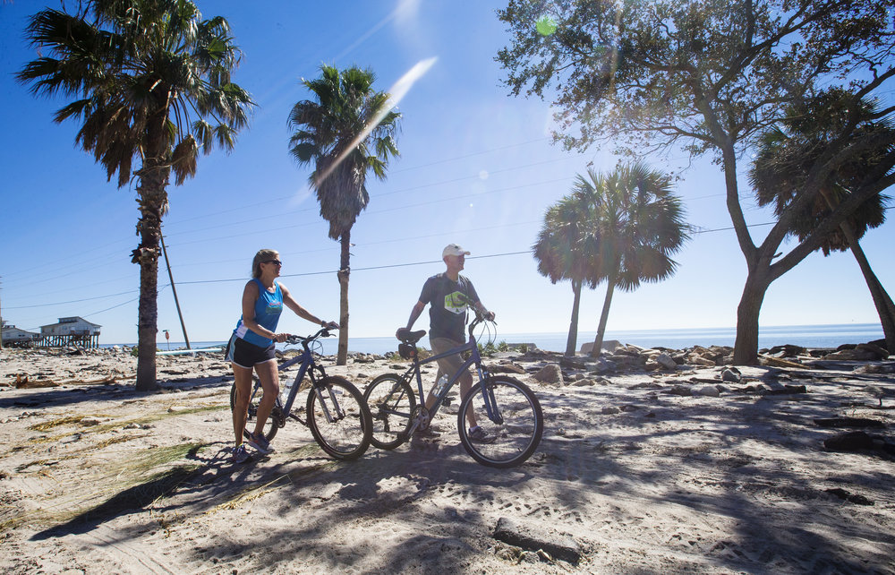 Rob and Connie Clark, walk their bikes around the destroyed portion of Alligator Drive in Alligator Point on October 12, 2018. With part of Alligator Drive undrivable, residents have to find alternative ways to get to their homes.