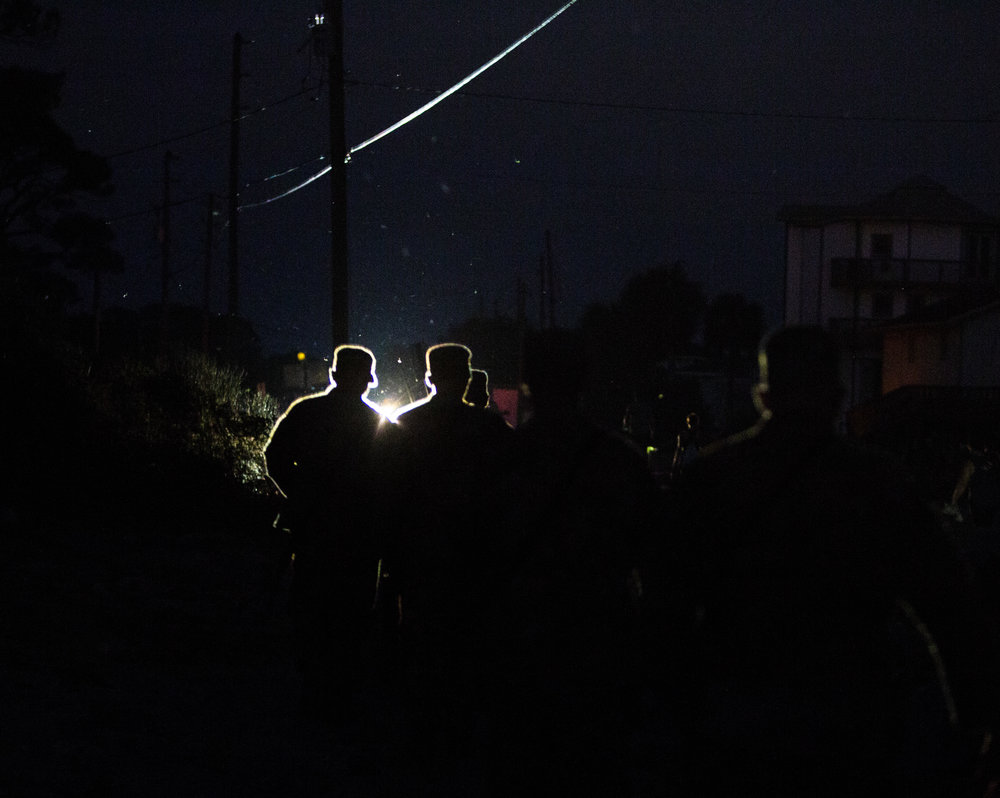 Members of Florida National Guard walk back to their trucks in the dark after patrolling Alligator Drive in Alligator Point on October 11, 2018, one day after Hurricane Michael hit the area. It may take weeks to restore power to parts of the Florida Panhandle.
