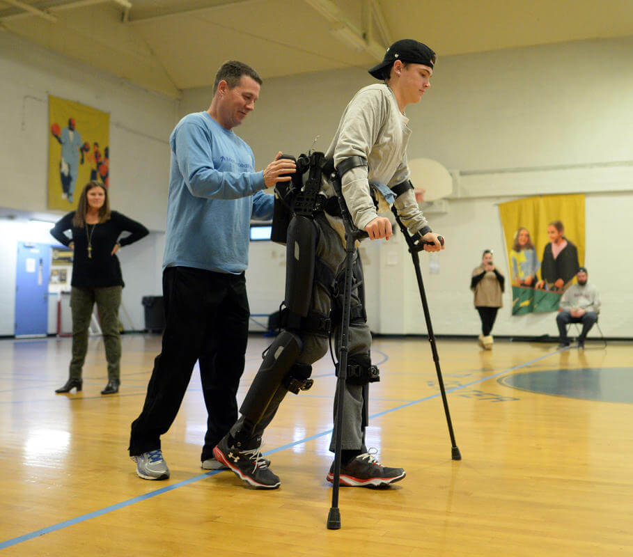Mark Delamere Jr., who was paralyzed from the waist down three years ago, uses an exoskeleton suit to walk in the gym at the Roche Family Community Center the West Roxbury neighborhood of Boston on Monday, November 21, 2016. He is spotted by his father Mark Sr., as his mother Sheila Delamere looks on. Boston Herald Staff photo by Christopher Evans