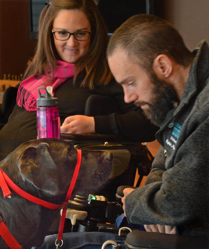 Credit: Chris Christo   FRIENDS IN ADVERSITY: Katie Tuscano watches as her mentor Ryan DeRoche interacts with his assistance dog Oliver at Spaulding Rehabilitation hospital in Charlestown.
