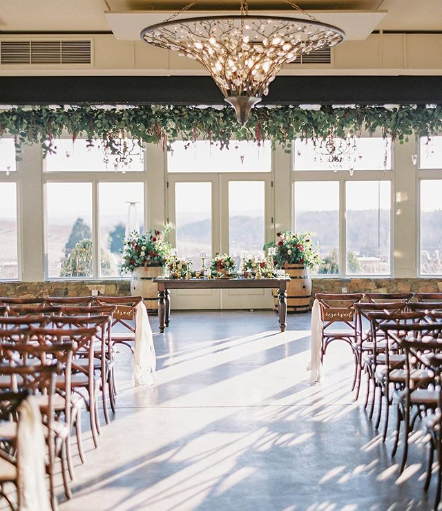 Winter indoor ceremony feels @stonetowerwinery || 🌿complete with the beautiful hanging greenery by: @hollychapple! 📷: @vickigrafton #martindowntheaisle