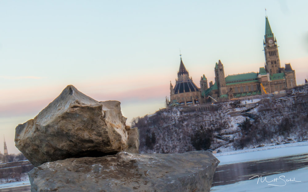 The Canadian Parliament peaking out from behind a pile of rocks at the tip of Victoria Island in Ottawa, Canada. Shot from a tripod with a Canon EOS M5 at 1/5, F/32, and ISO200.