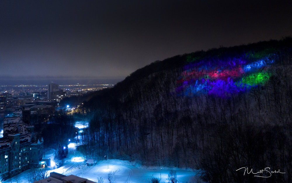 """Aurores Montreal"" projections on   Mont Royal in Montreal, QC. Panorama compilation of two shots from an airborne DJI Mavic at .5sec, F/2.2 and ISO 200."