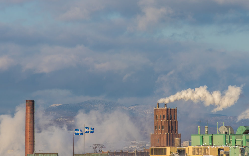 Factories cutting through the morning fog, in front of the Laurentian Mountains north of Quebec City, Quebec. Shot with a Canon EOS 5M and 70-300MM at 180MM, 1/640, F/5.6 and ISO 100.