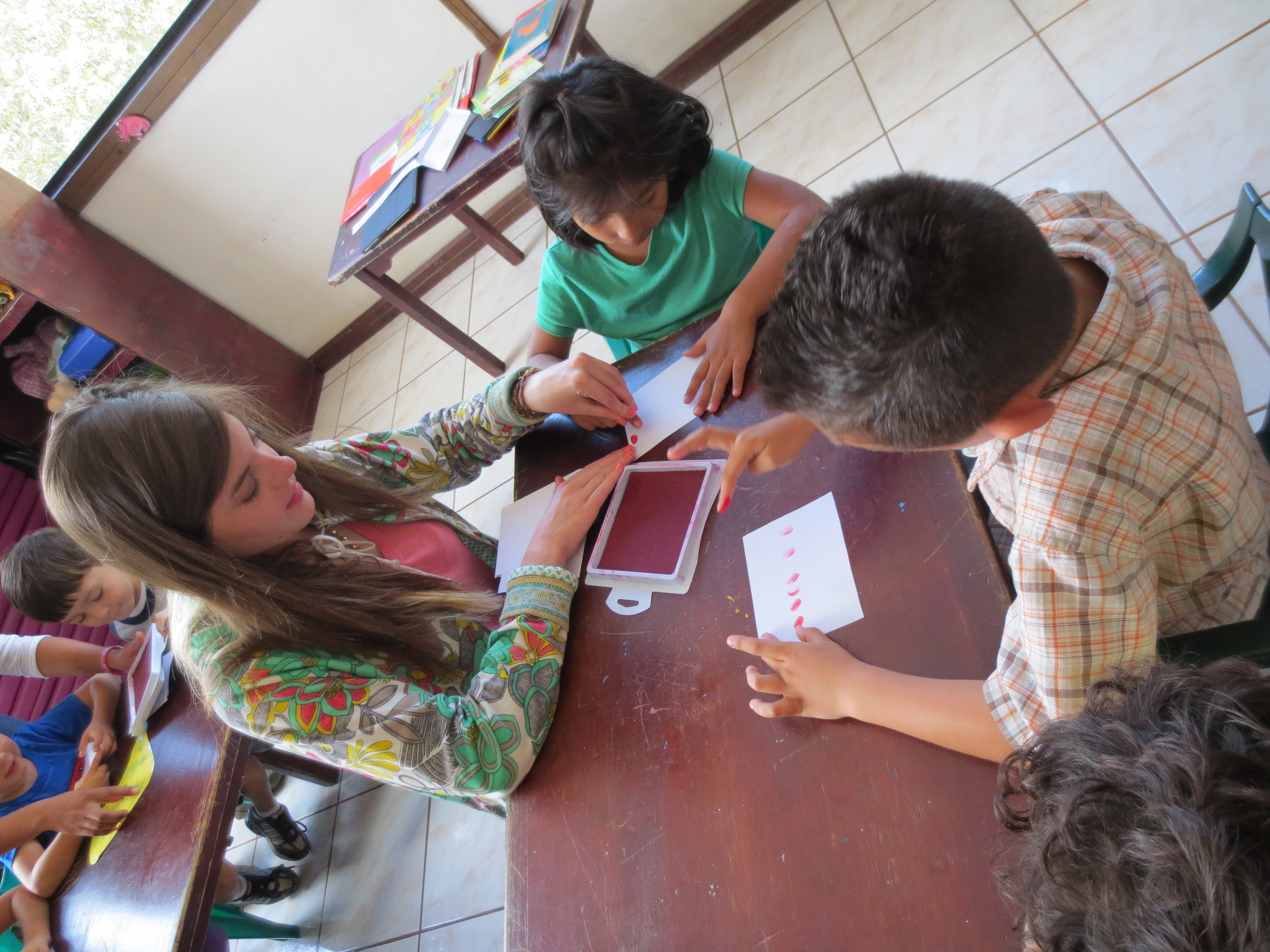 """Lexi is helping some of the kids with their """"B U G"""" craft."""