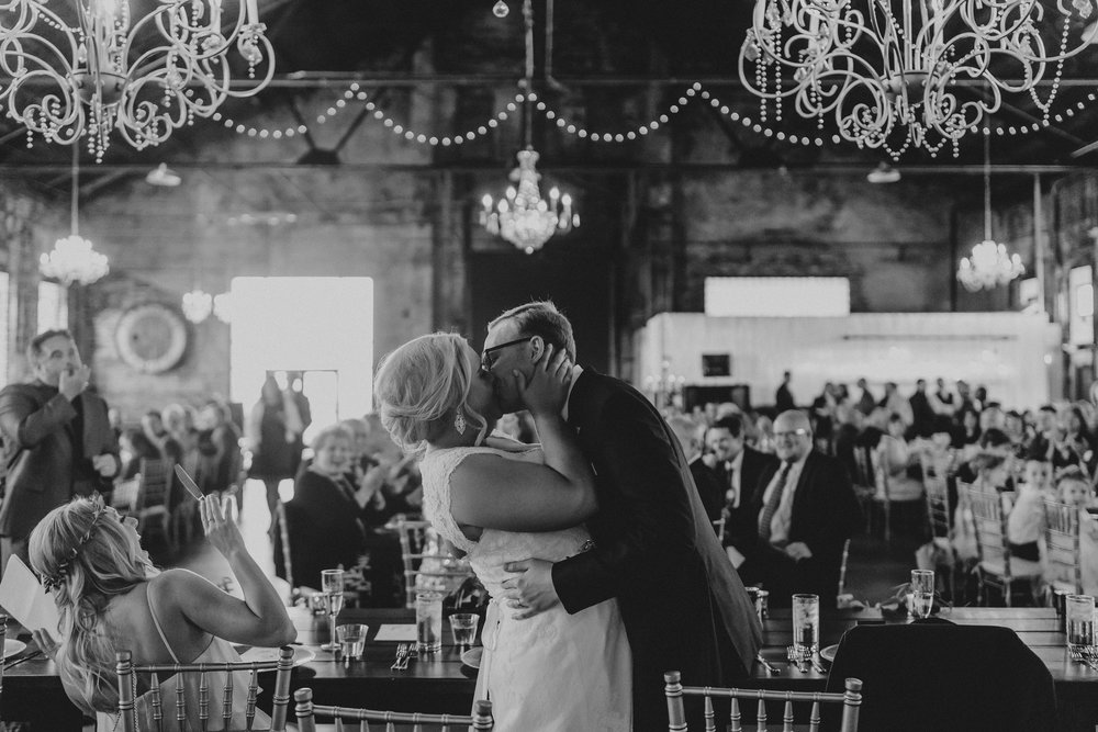 melissa wedding andrew kissing her at table under chandeliers horz.jpg