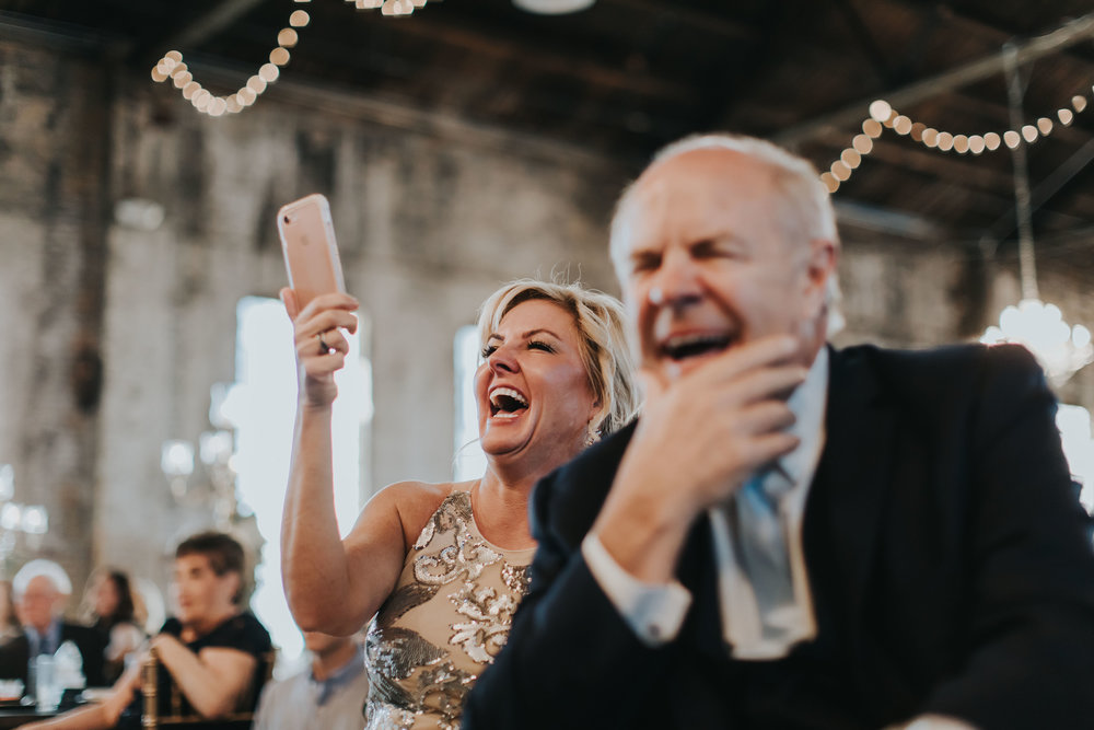 melissas mom holding up phone during reception.jpg
