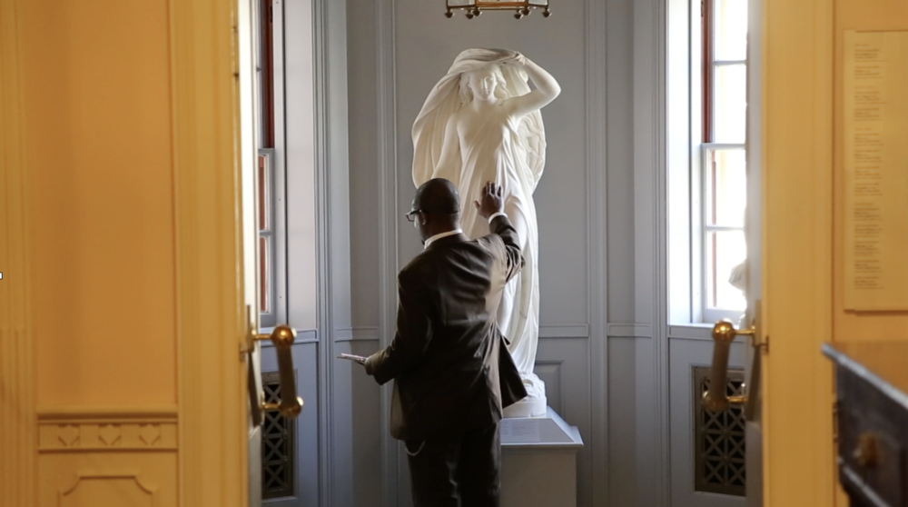 A guest critic touches a marble statue when the guard is not looking.