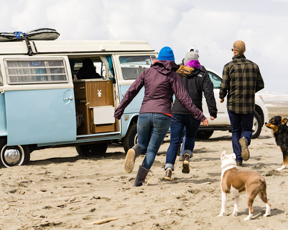 group of friends running toward a camper van on the beach