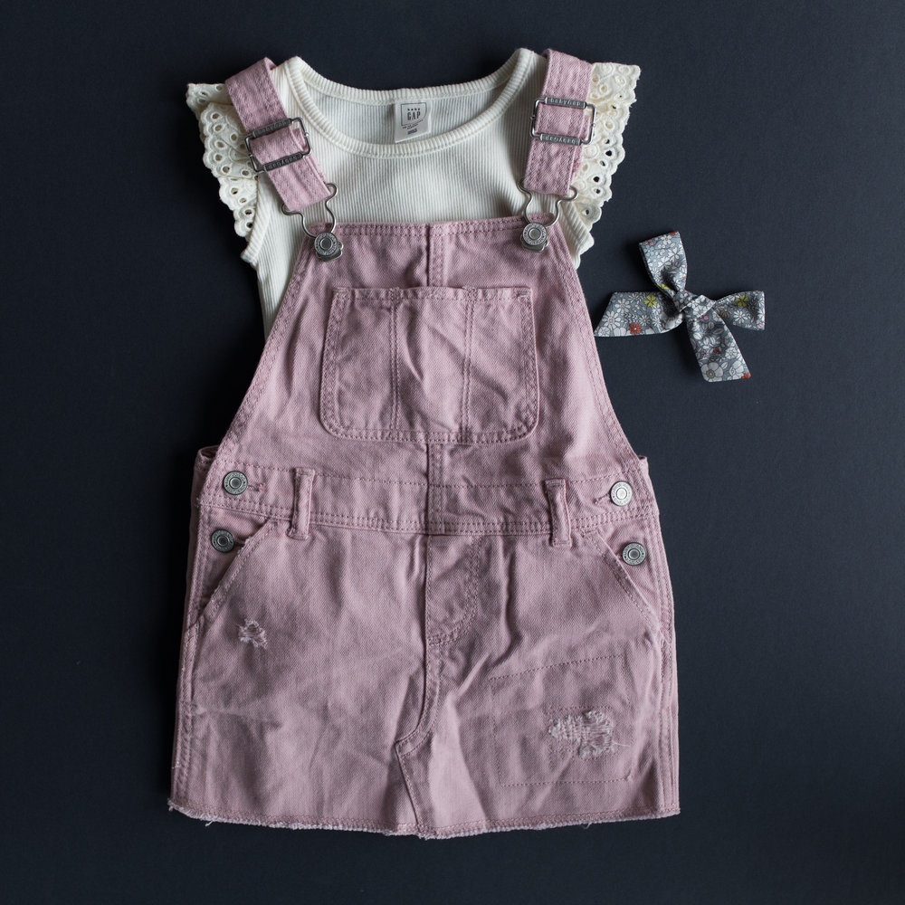 Pink denim skirt overalls $19.99 with an ivory ruffle top $7.97 both from Gap!   http://www.gap.com/browse/product.do?cid=65269&pcid=65263&vid=1&pid=654209002    http://www.gap.com/browse/product.do?cid=65271&pcid=65263&vid=1&pid=577563002