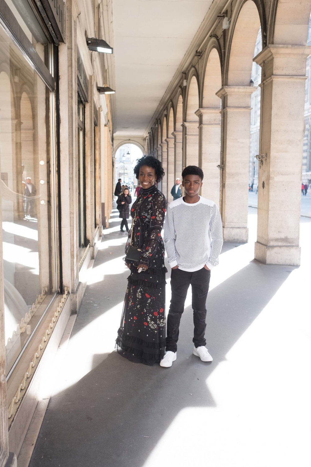Adorable mother and son posing outside the Louvre Museum in Paris