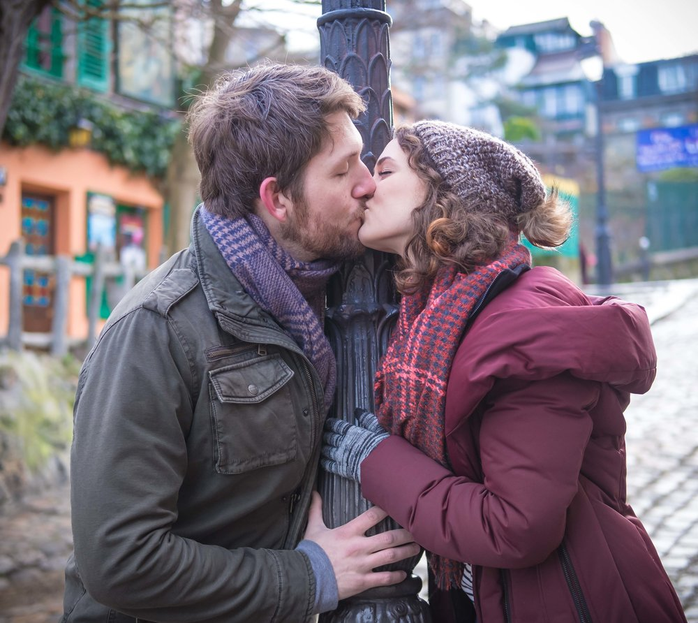 Newly engaged couple kissing in Montmartre in Paris