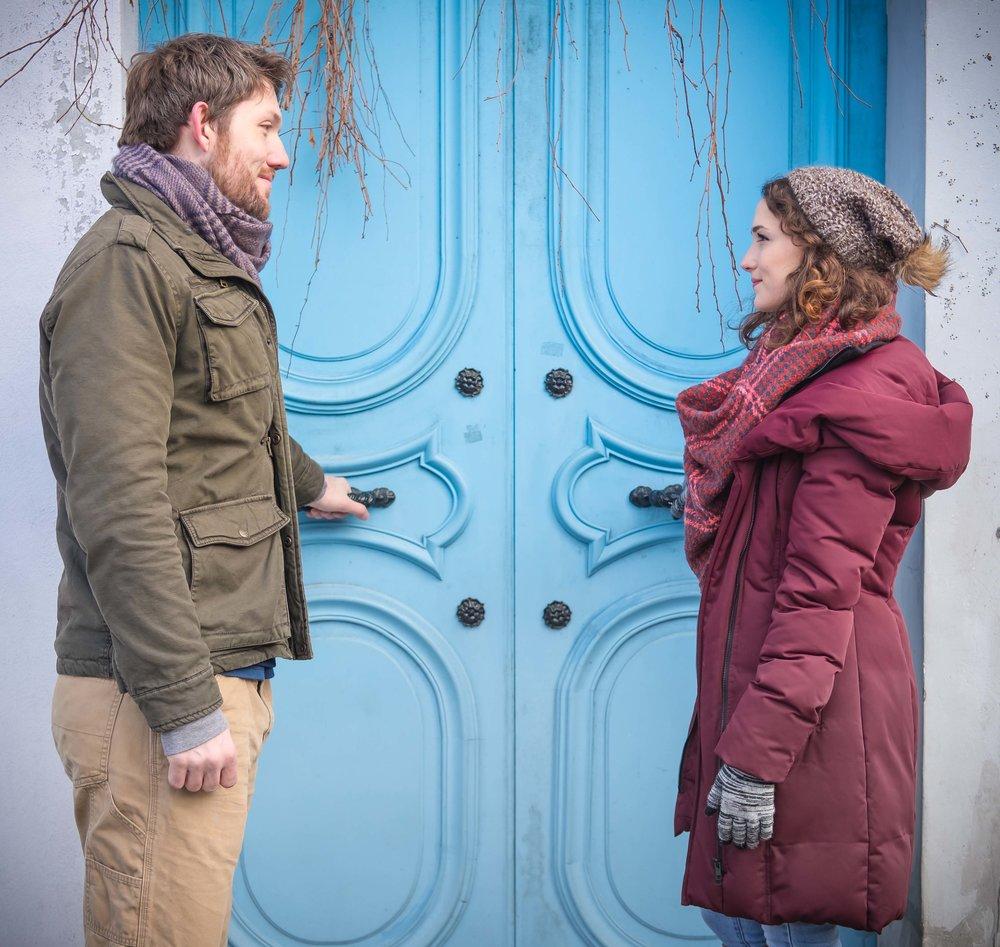 Couple in love posing in front of blue door in Paris