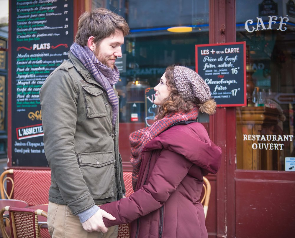 Couple in love in front of a quaint Paris cafe