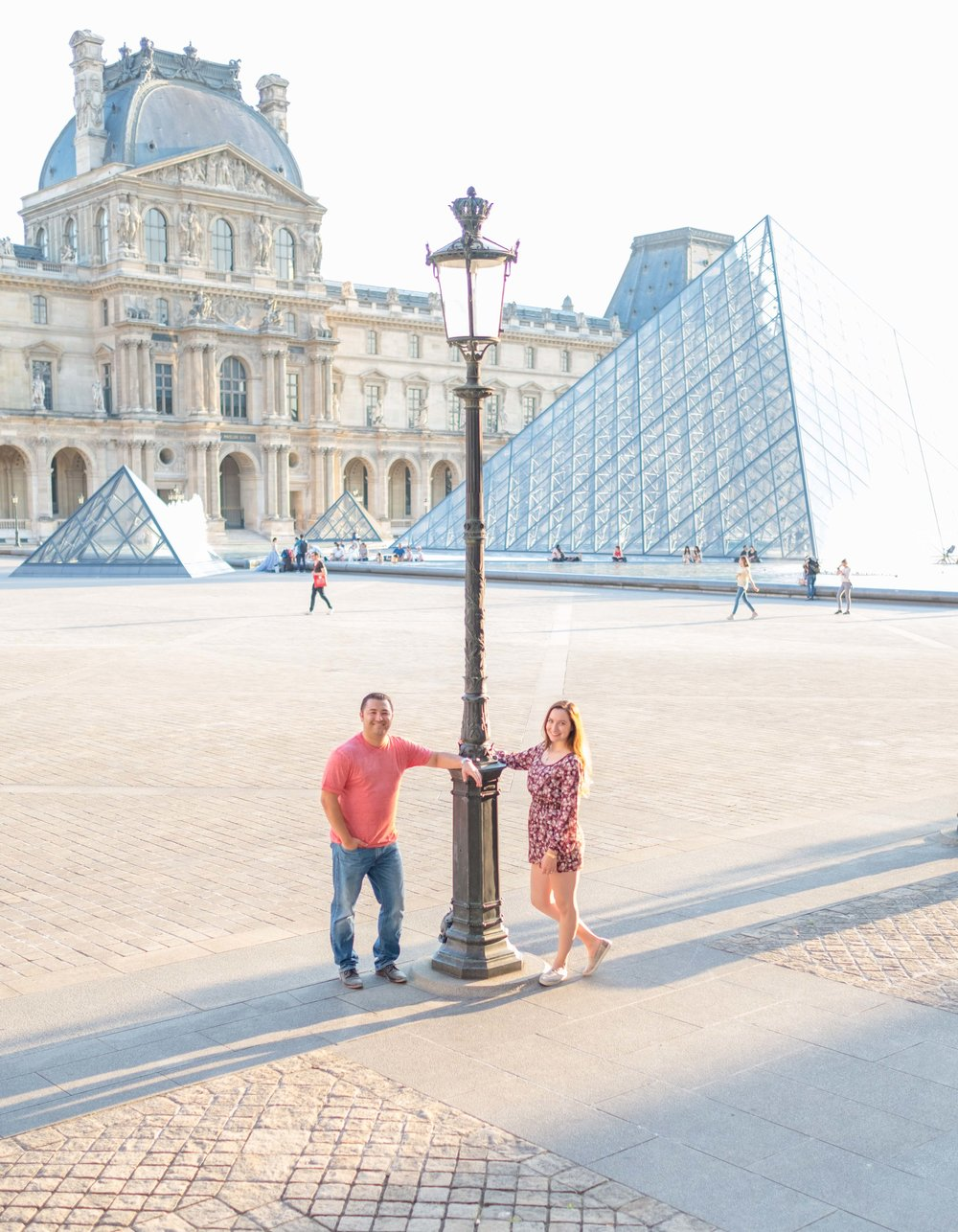 Engaged couple posing at Louvre Museum in Paris