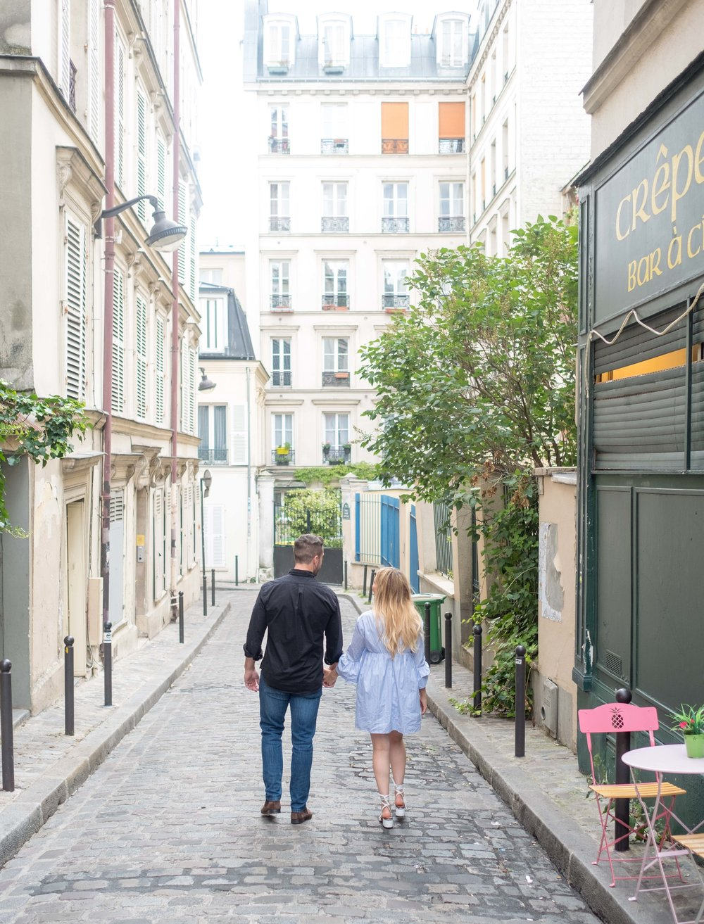 Engaged couple walking hand in hand in Paris