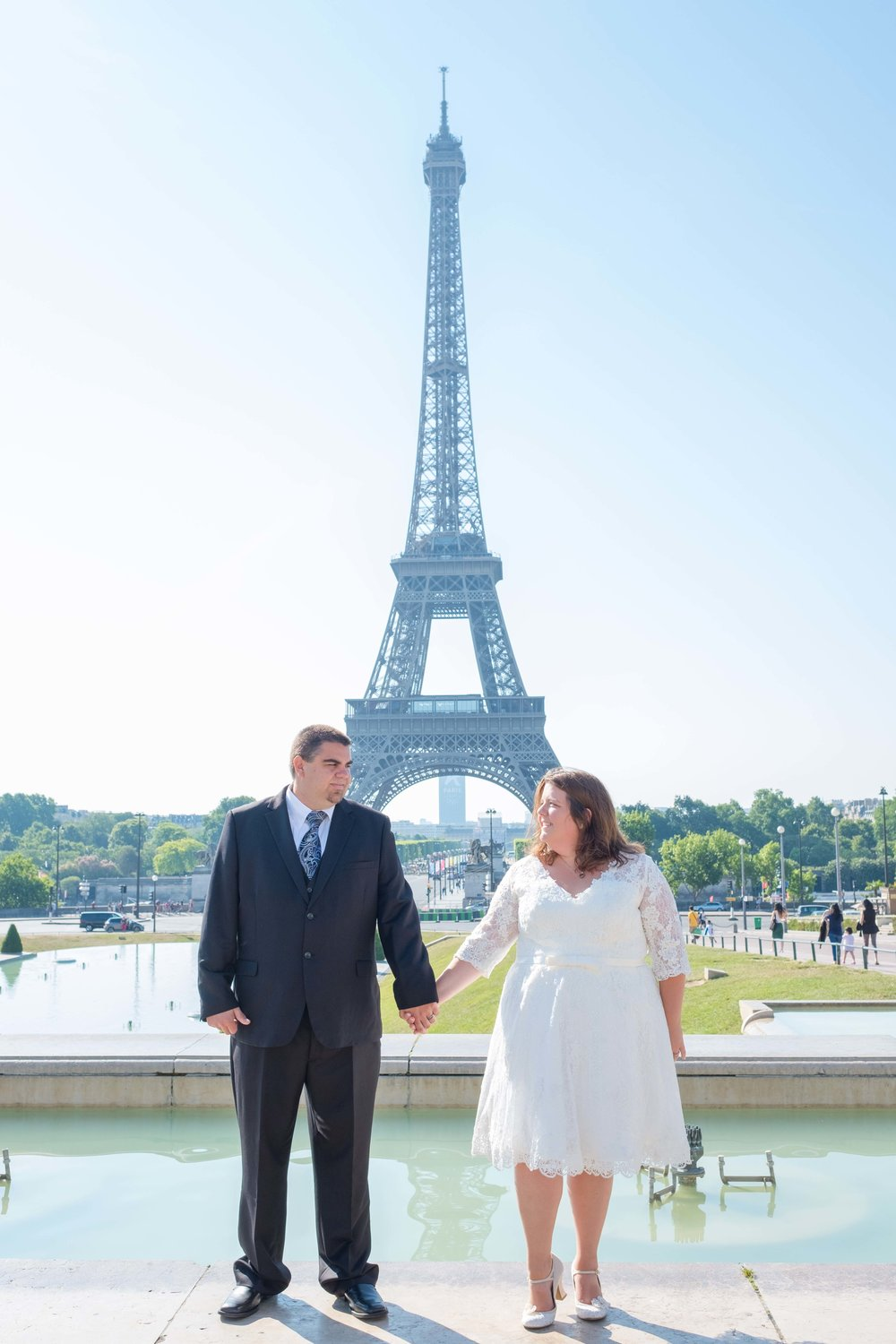 Newlyweds holding hands in Paris with Eiffel Tower in background