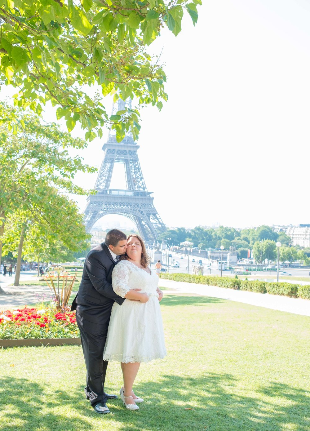 Newlyweds kissing near the Eiffel Tower in summer