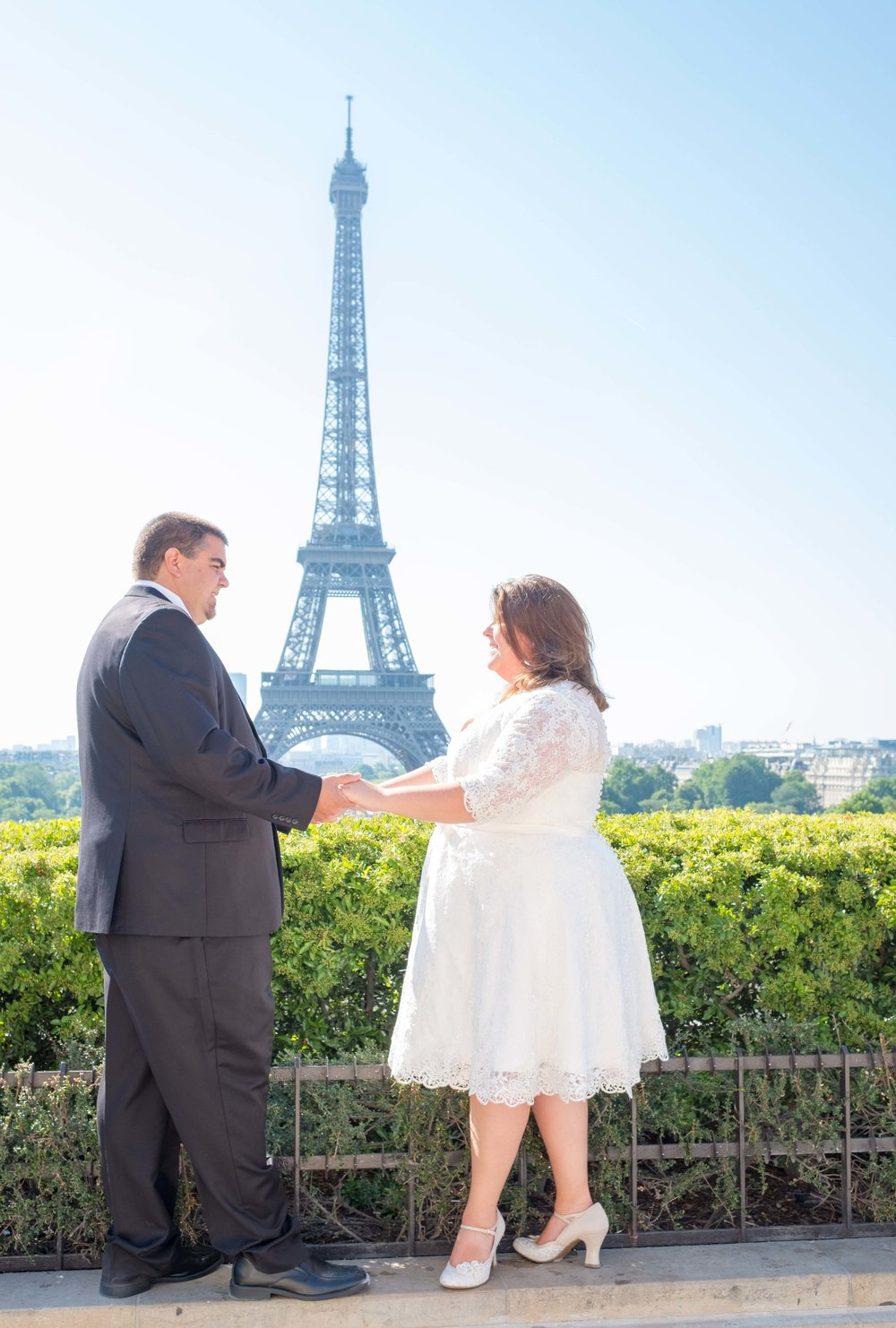 Newlywed couple holding hands with the Eiffel Tower in the background
