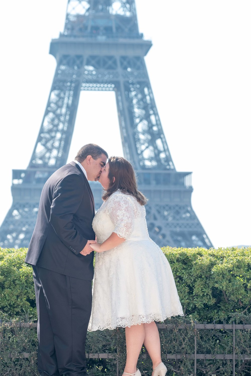 Newlyweds holding hands in front of the Eiffel Tower in Paris