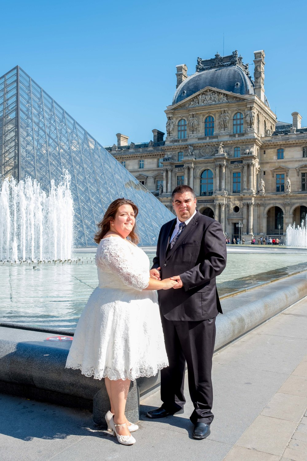 Newlyweds in front of the Louvre Museum in Paris