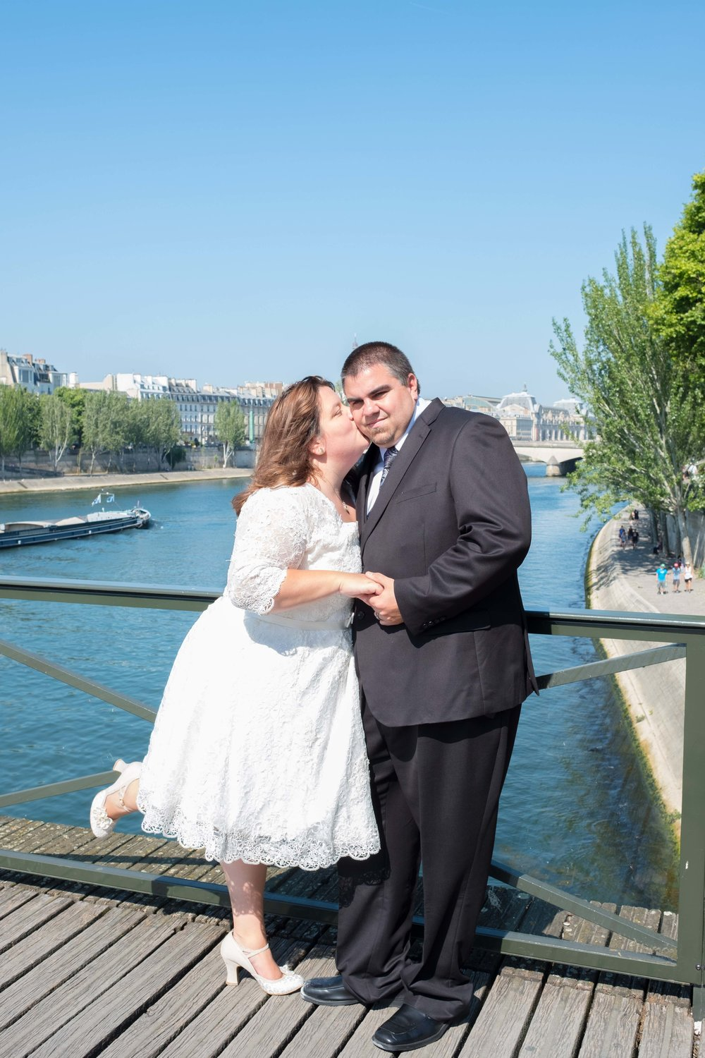 Newlyweds kissing on a bridge in Paris