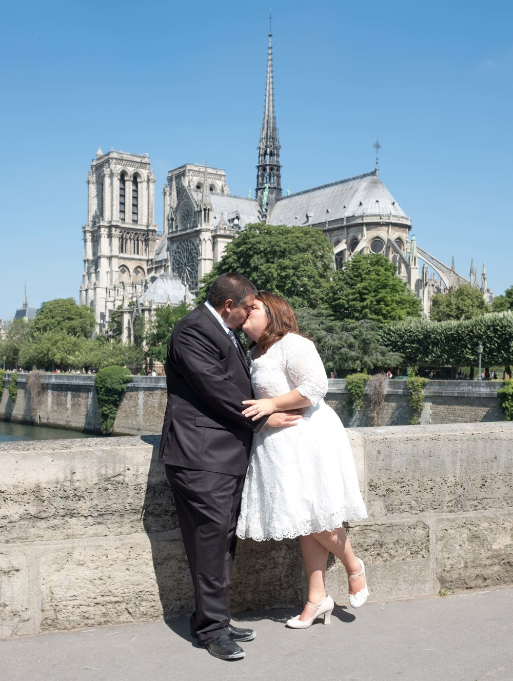 Newlyweds kissing outside of the Notre Dame Cathedral in Paris