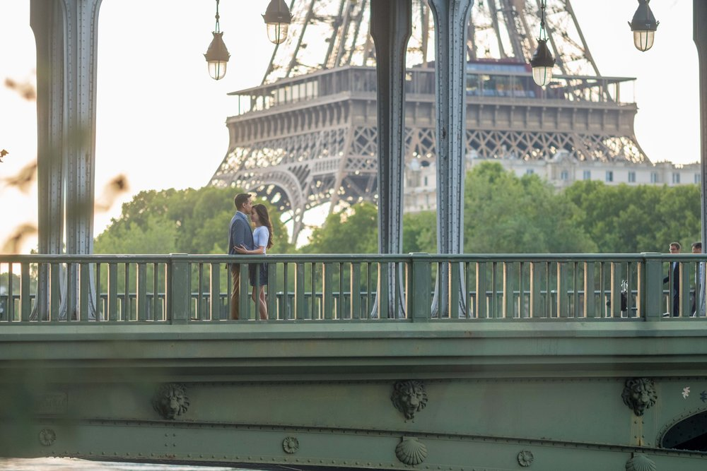 Couple standing on bridge in Paris after getting engaged