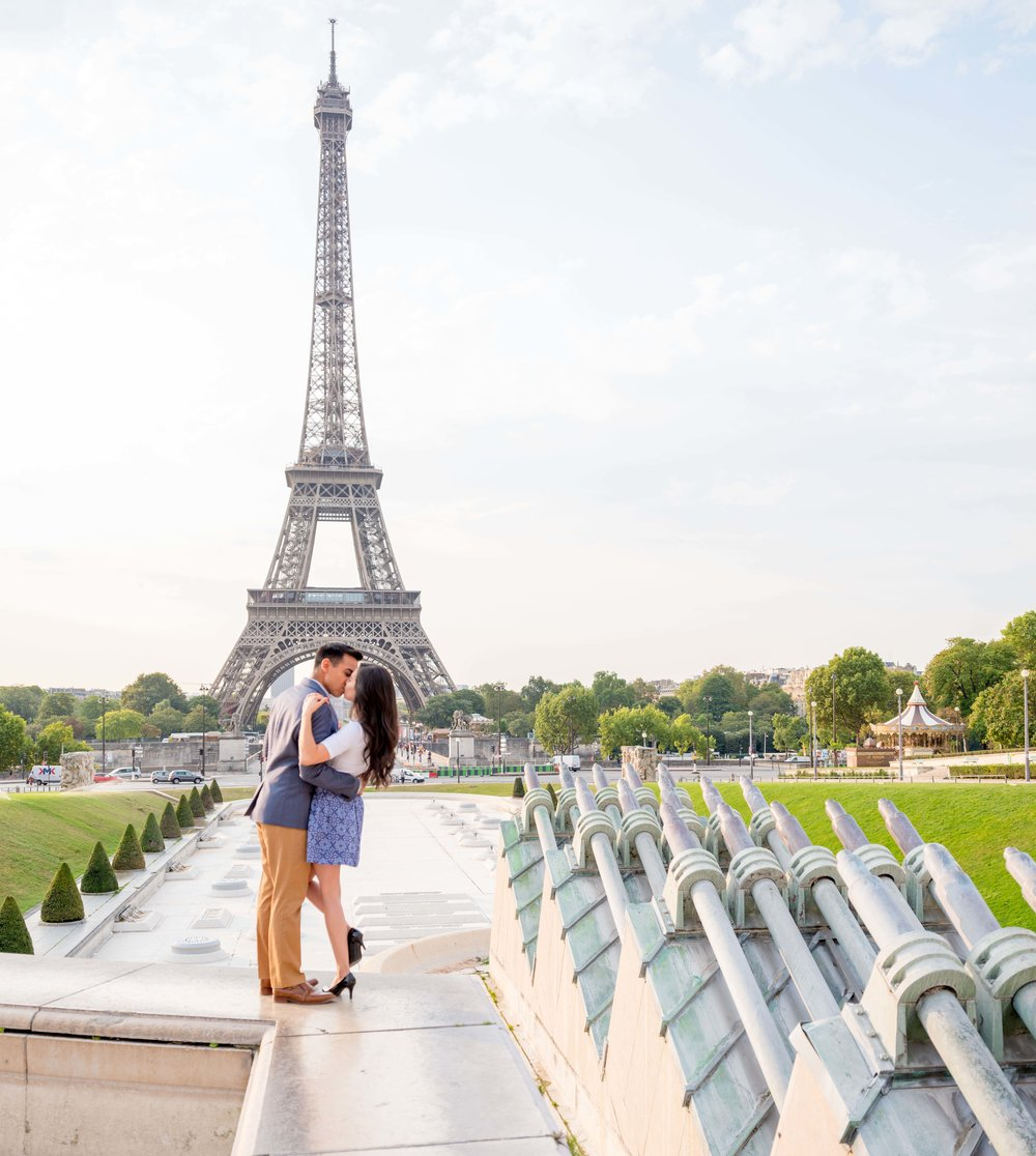 Engaged couple kissing in front of the Eiffel Tower in Paris