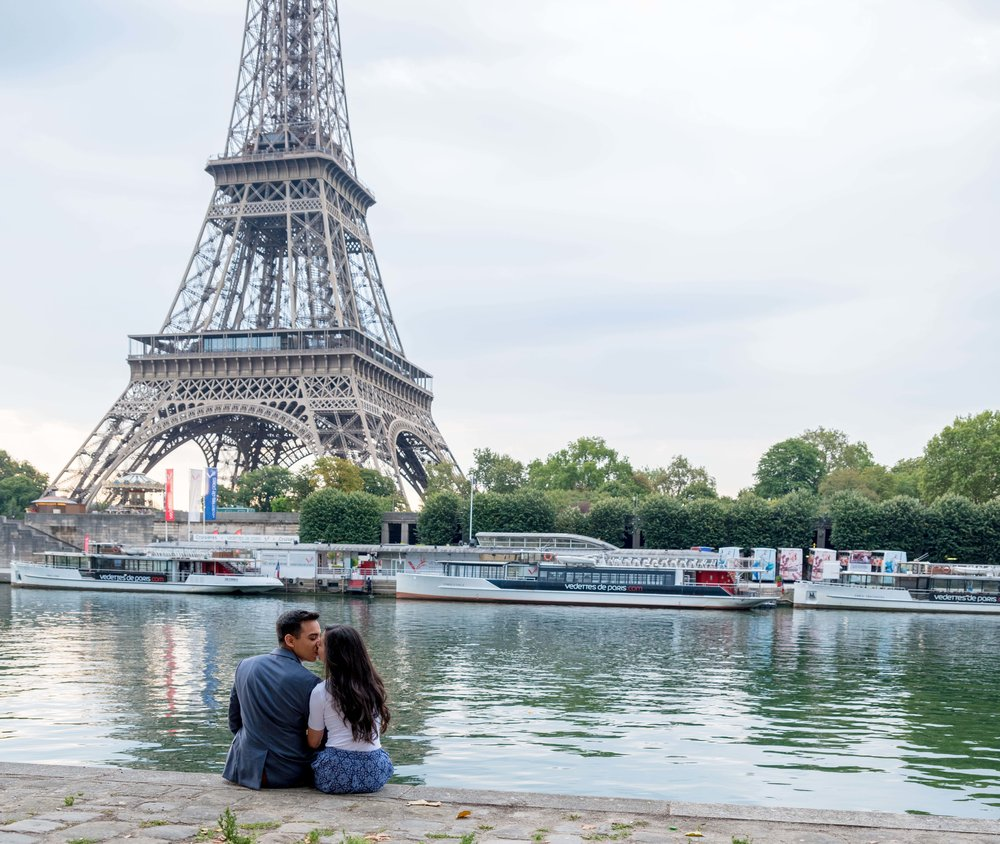Romantic couple sitting by river in Paris overlooking Eiffel Tower