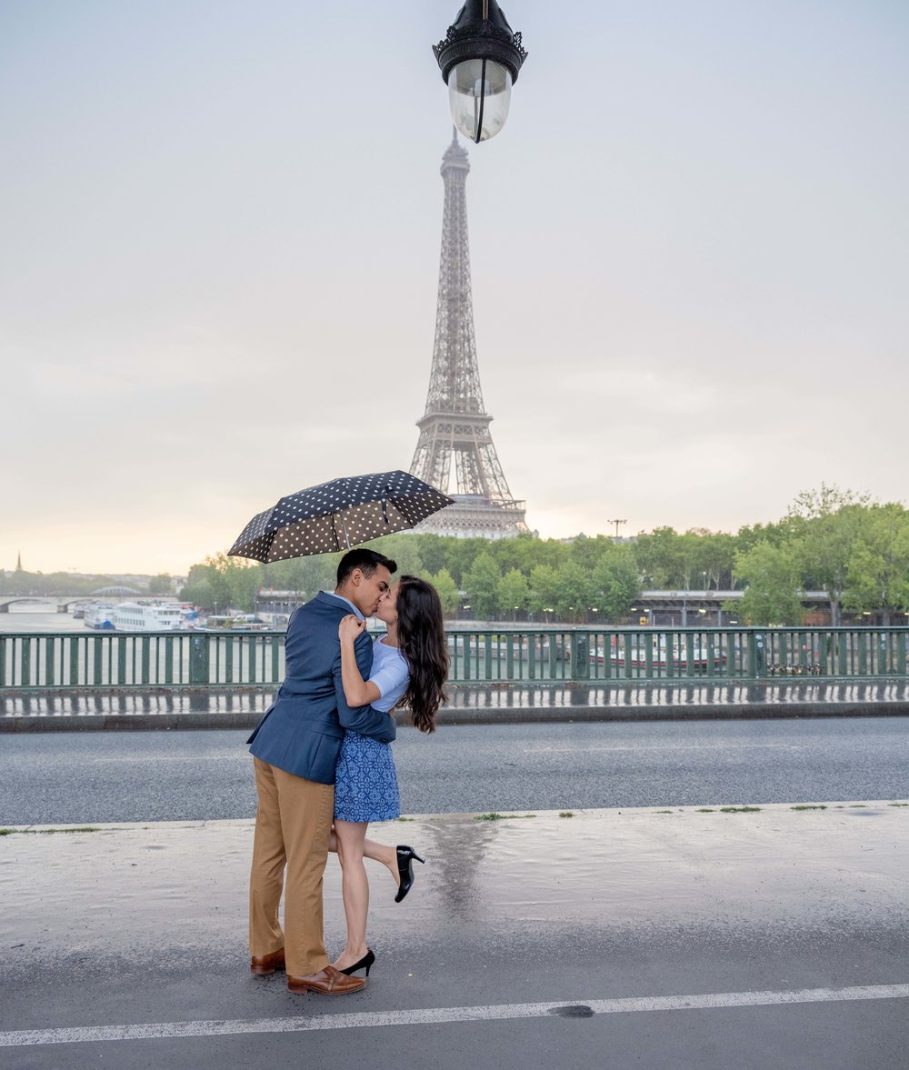 Romantic couple in rain in Paris with view of Eiffel Tower