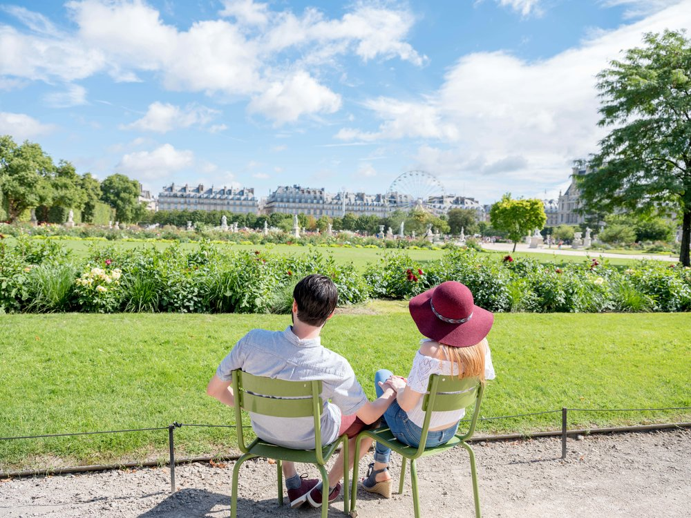 engaged couple sitting in garden in paris
