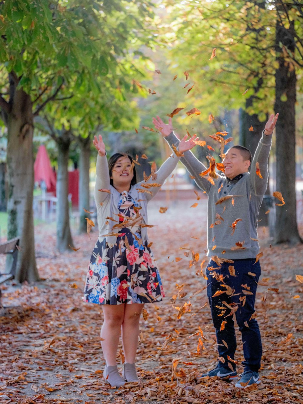asian couple throwing leaves in paris park