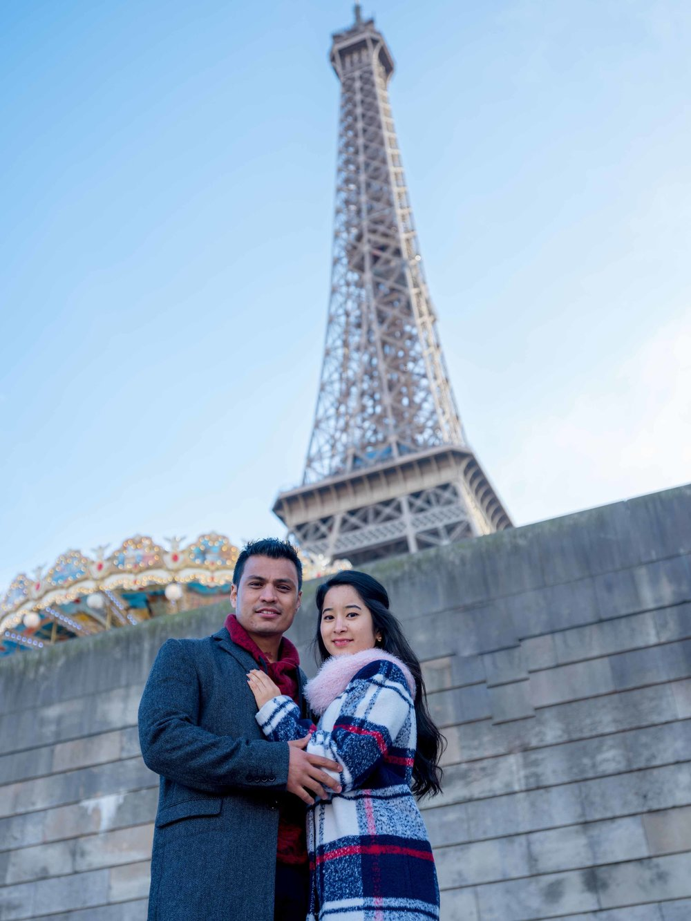 engaged couple at eiffel tower in paris with carousel
