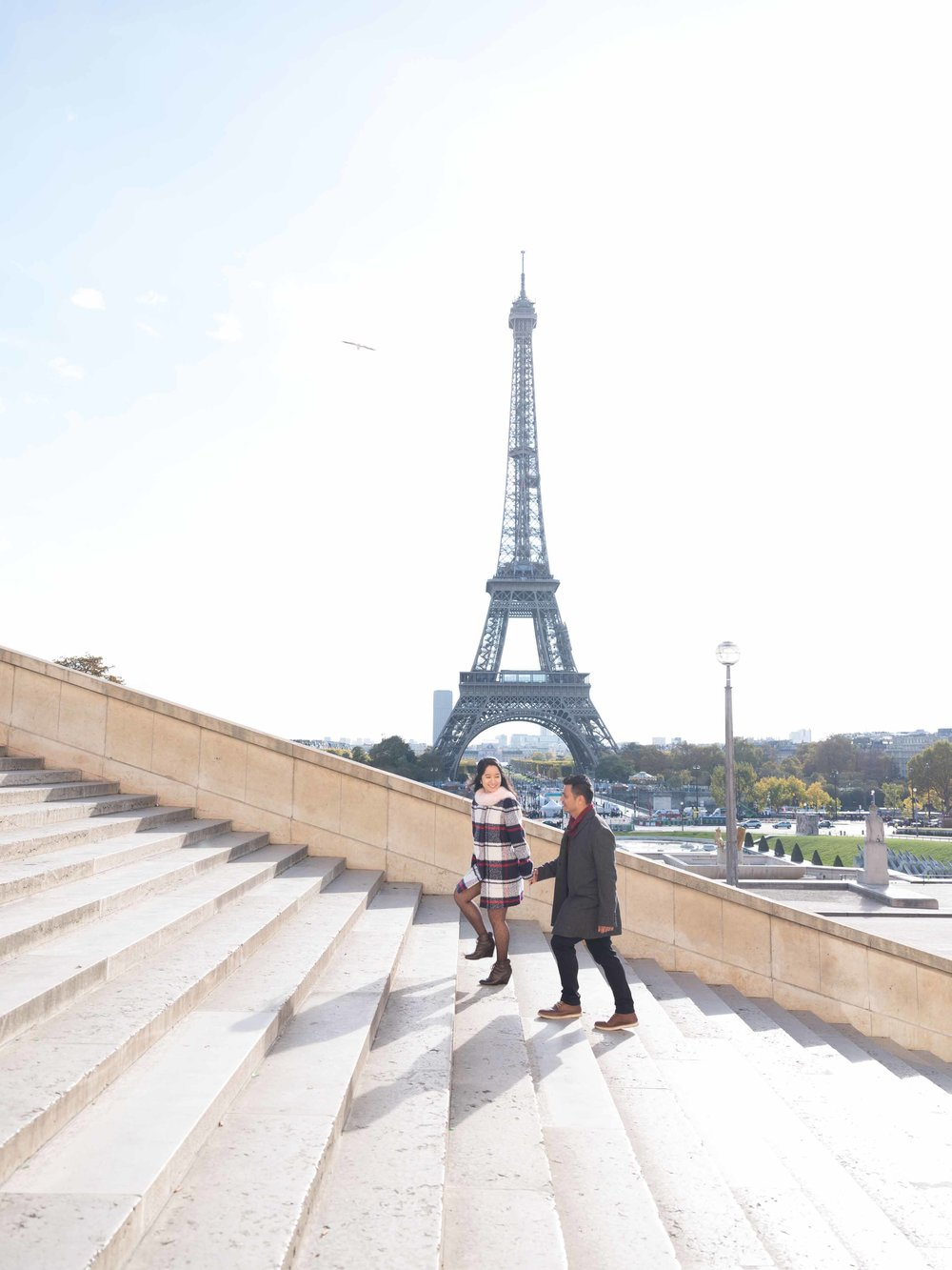 engaged couple walking up steps at eiffel tower paris