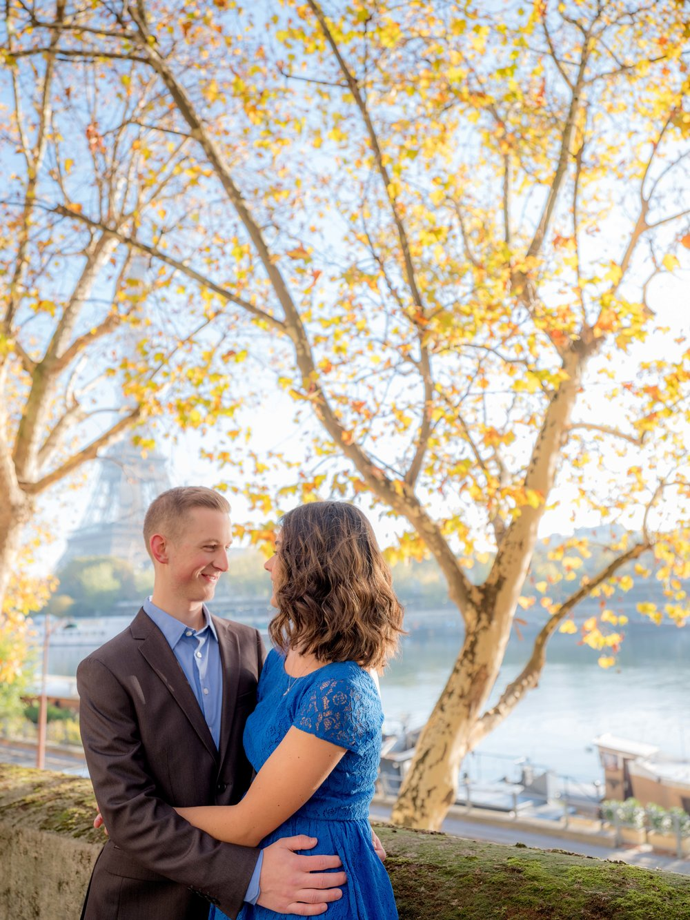 romantic young couple engagement in autumn with view of eiffel tower