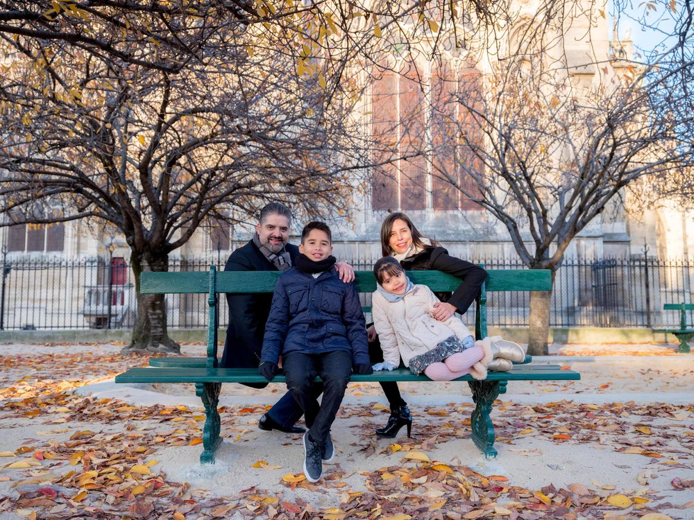 family in pqris in autumn on park bench