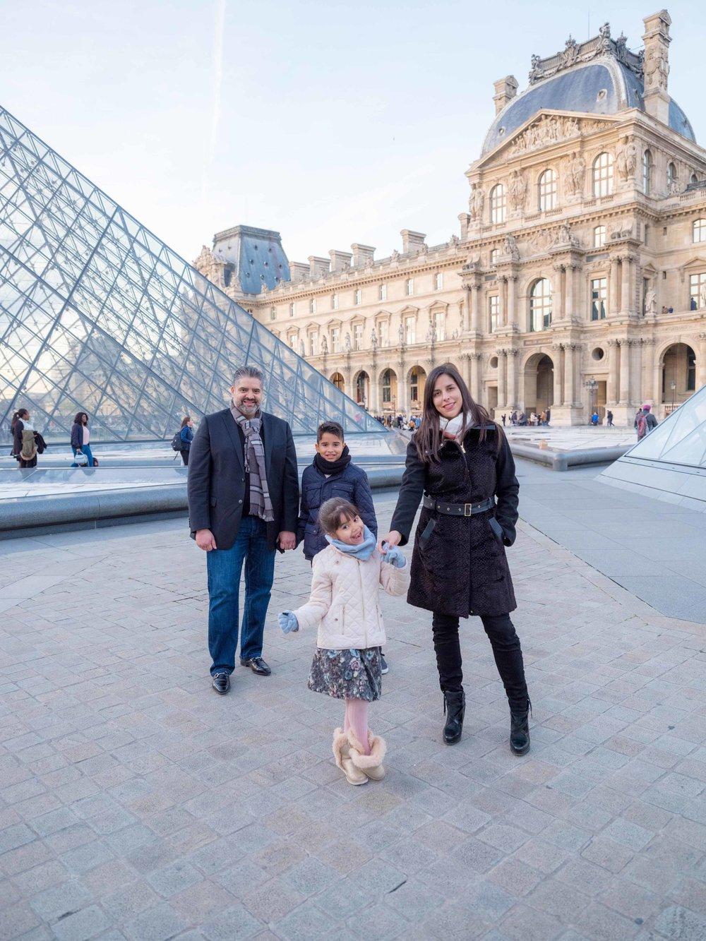family in pqris in autumn at louvre museum
