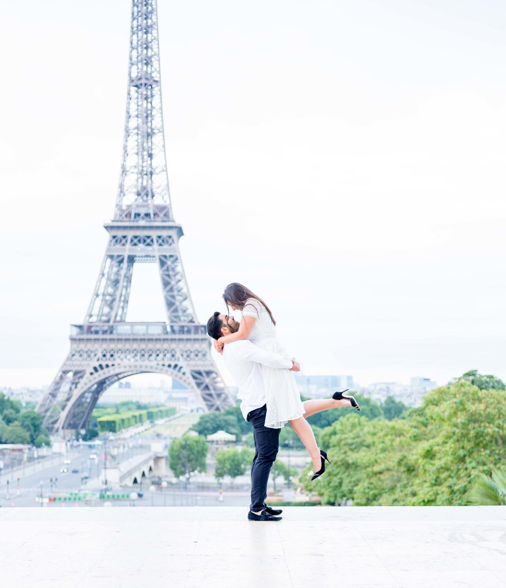 beautiful newly engaged couple in white at eiffel tower paris