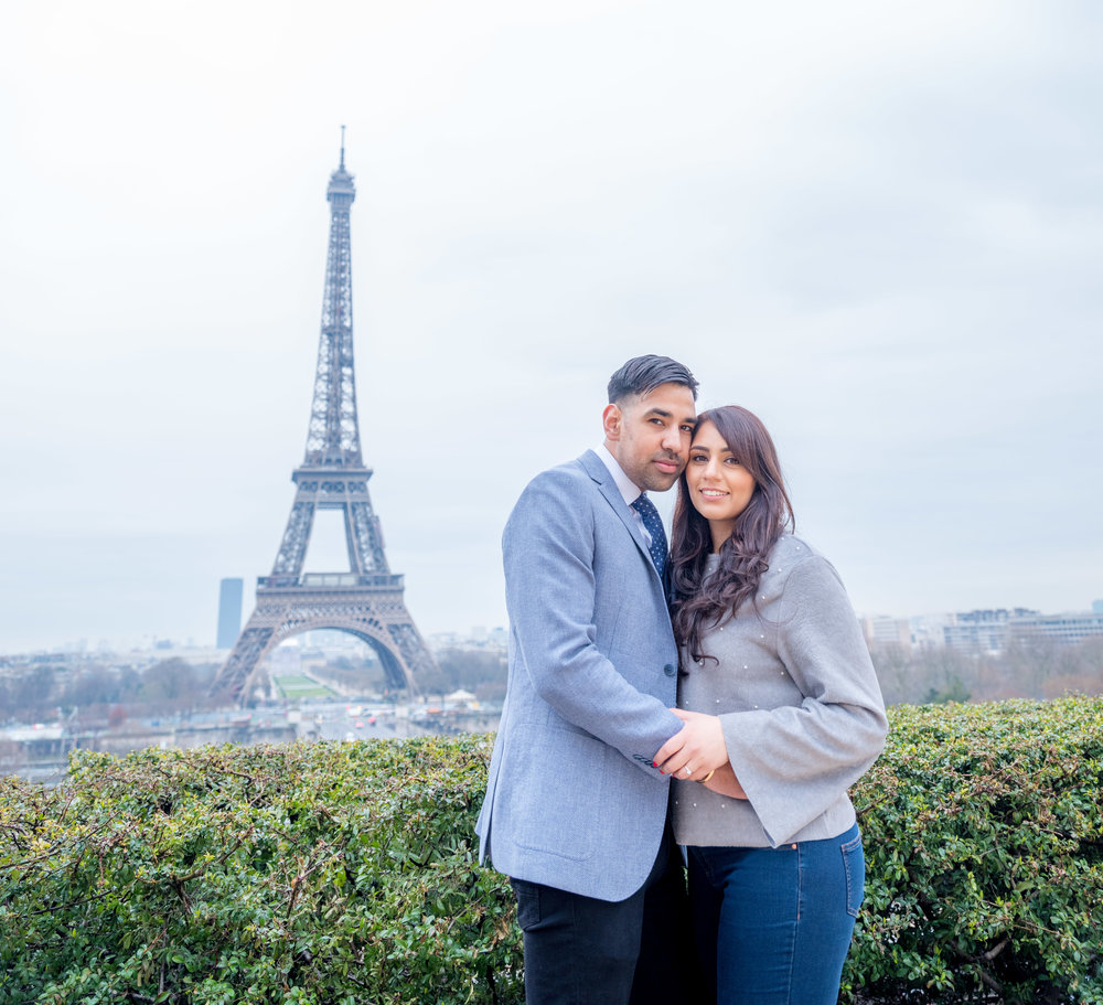 surprise proposal at the eiffel tower in paris france on a rainy day