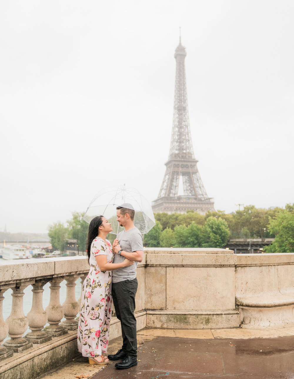 rainy couples engagement photo shoot in paris france at the eiffel tower
