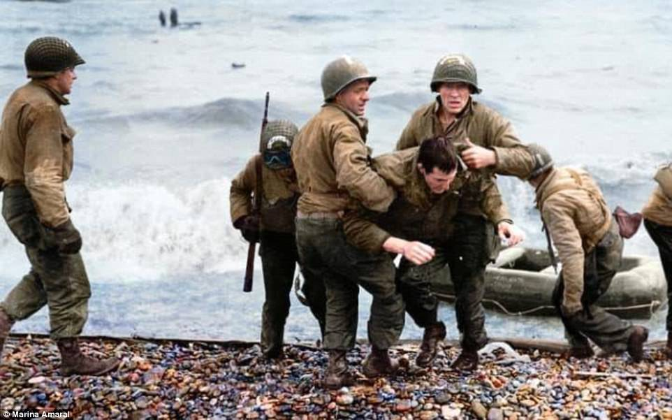 D-Day medics From America's 5th and 6th Engineer Special Brigade help wounded soldiers as they reach Omaha Beach. In the background, survivors of sunken landing craft who reached the beach by using a life raft are helped ashore