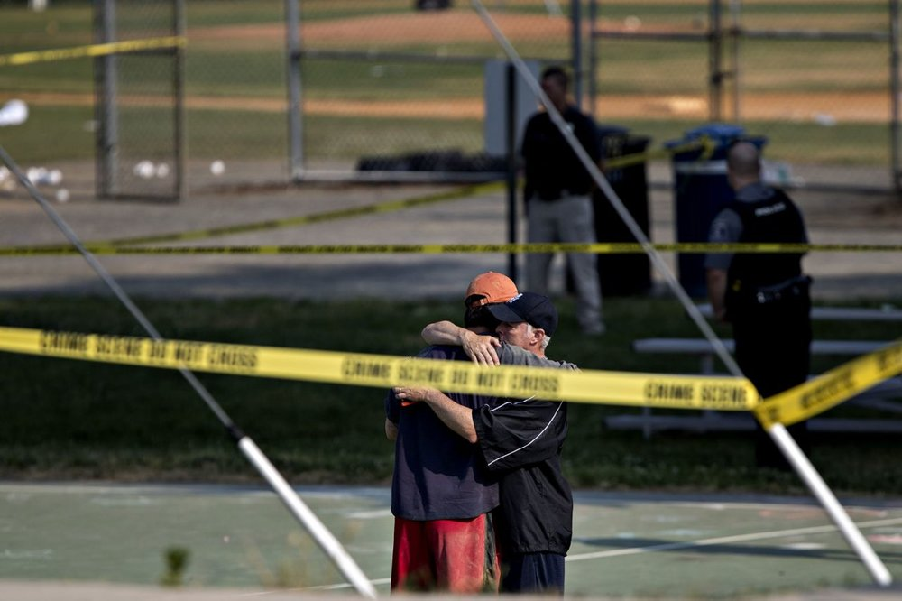 Two people hug in front of police crime scene tape following a shooting
