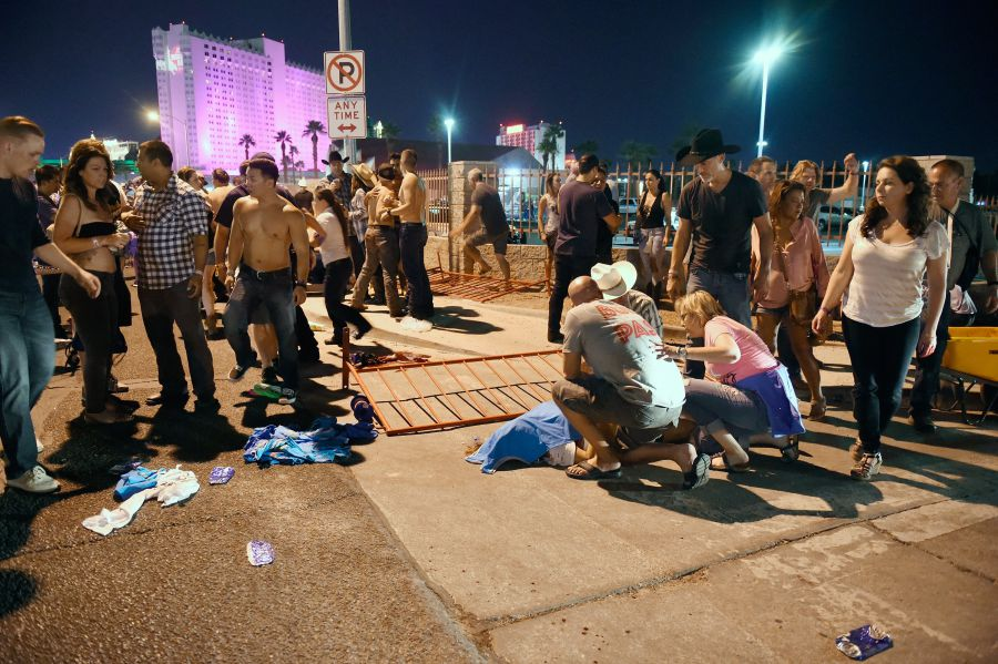 People tend to the wounded outside the Route 91 Harvest Country music festival grounds after an apparent shooting on October 1, 2017 in Las Vegas, Nevada. There are reports of an active shooter around the Mandalay Bay Resort and Casino. (Photo by David Becker/Getty Images)