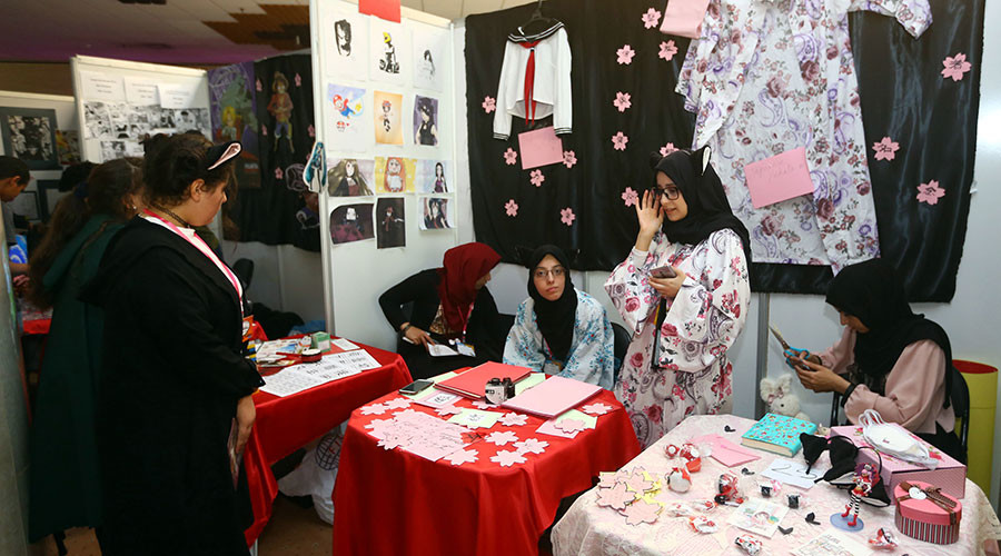 People walk past a stall during the Libya Comic Convention © Mahmud Turkia / AFP