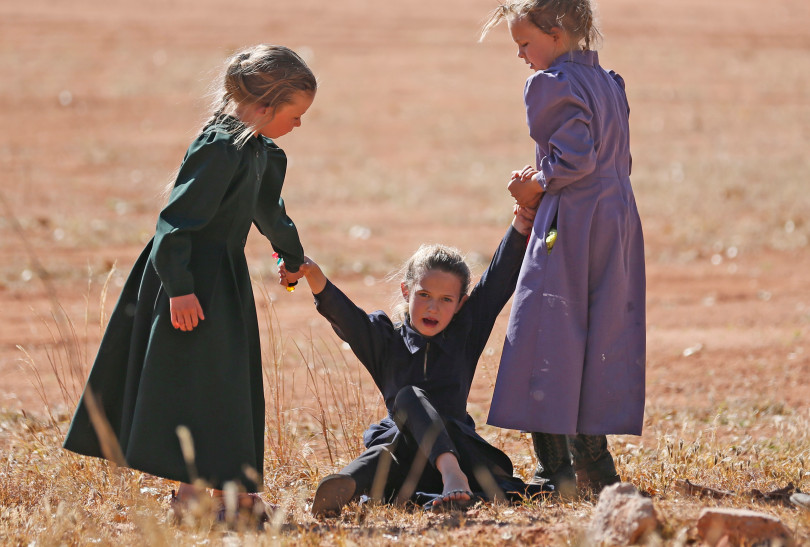 In this Wednesday, Oct. 25, 2017 photo, young girls play together in Colorado City, Ariz. The community on the Utah-Arizona border has been home for more than a century to a polygamous sect that is an offshoot of mainstream Mormonism. The community is undergoing a series of changes as the sect's control of the town slips away amid government evictions and crackdowns.