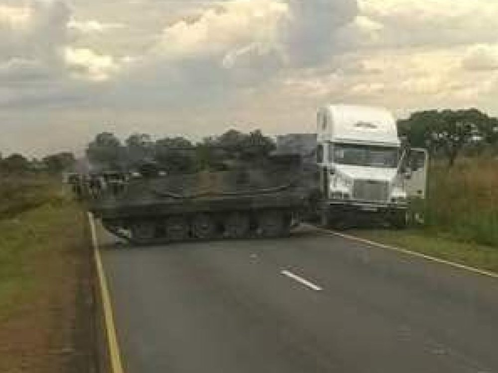 An armoured personnel carrier manoeuvres along the road between Norton and Harare