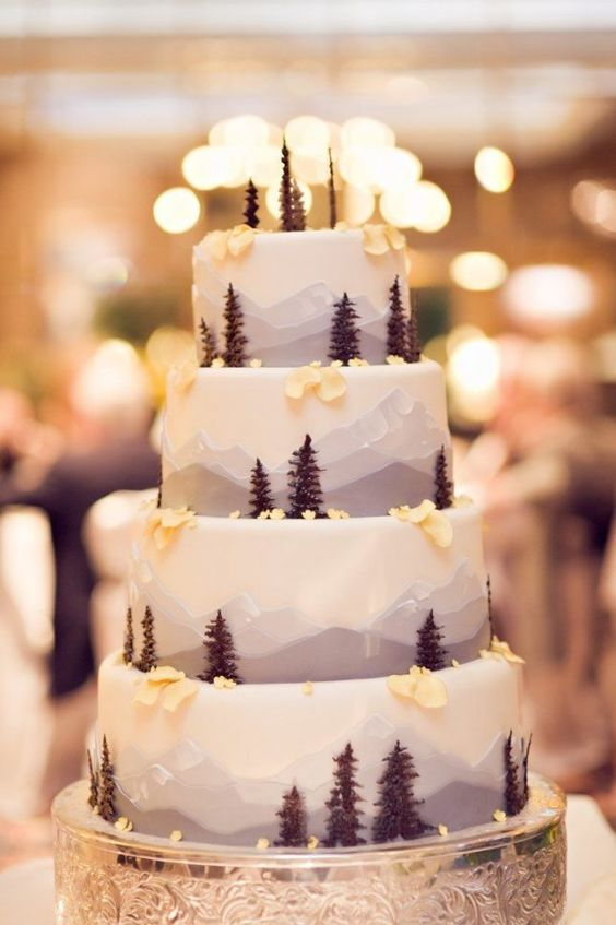 How about this magical winter wedding cake that incorporates the majesty of winter, snow-covered peaks with beautiful pine trees.