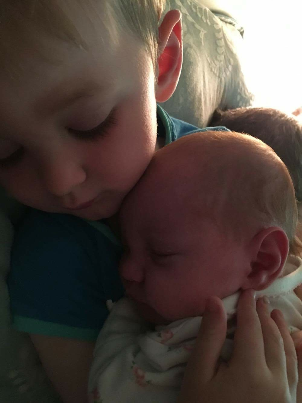 big brother cuddles baby sister