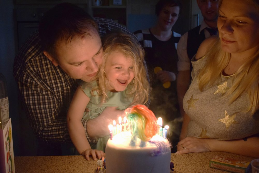 blonde toddler blowing out birthday candles © mebecomingmum